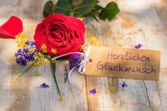 Η κάρτα με το γερμανικό κείμενο, Herzlichen Glueckwunsch, συγχαρητήρια μέσων και κόκκινος αυξήθηκε λουλούδι στοκ εικόνα με δικαίωμα ελεύθερης χρήσης