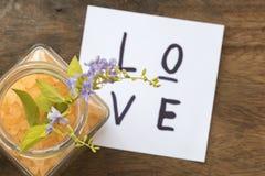Η κάρτα μηνυμάτων αγάπης και το αλατισμένο άρωμα SPA όλων των λουλουδιών ξεφλουδίζουν τα τρόφιμα με τα πορφυρά λουλούδια Στοκ Φωτογραφία