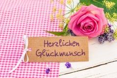 Η κάρτα συγχαρητηρίων με το γερμανικό κείμενο, Herzlichen Glueckwunsch, συγχαρητήρια μέσων και ρόδινος αυξήθηκε λουλούδι στοκ φωτογραφία με δικαίωμα ελεύθερης χρήσης