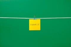 Η κίτρινη σημείωση εγγράφου για τη σκοινί για άπλωμα με το κείμενο ευχαριστεί το U Στοκ φωτογραφία με δικαίωμα ελεύθερης χρήσης