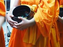 Η κίτρινη τήβεννος ένδυσης μοναχών που κρατά τις μαύρες ελεημοσύνες κυλά για τα τρόφιμα που προσφέρουν το πρωί στοκ φωτογραφίες