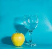 Η κίτρινη Apple με ένα ποτήρι του νερού σε ένα μπλε υπόβαθρο Στοκ φωτογραφία με δικαίωμα ελεύθερης χρήσης