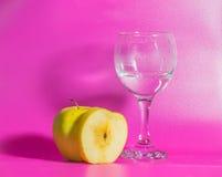 Η κίτρινη Apple με ένα ποτήρι του νερού σε ένα ρόδινο υπόβαθρο Στοκ φωτογραφία με δικαίωμα ελεύθερης χρήσης
