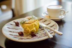 Η κίτρινη Apple, που γεμίζεται με τις σταφίδες και που ψήνεται με το σιρόπι μελιού Ψημένα επιδόρπιο μήλο και φλιτζάνι του καφέ φρ Στοκ Εικόνα
