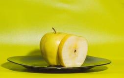 Η κίτρινη Apple σε ένα πιάτο σε ένα πράσινο υπόβαθρο Στοκ φωτογραφίες με δικαίωμα ελεύθερης χρήσης