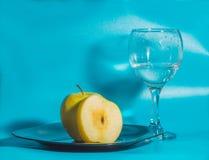 Η κίτρινη Apple στο πιάτο με ένα ποτήρι του νερού σε ένα μπλε backgr Στοκ εικόνα με δικαίωμα ελεύθερης χρήσης