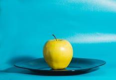 Η κίτρινη Apple στο πιάτο σε ένα μπλε υπόβαθρο Στοκ Φωτογραφίες