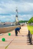 Η καθαρίζοντας γυναίκα πλένει το ανάχωμα του ποταμού Neva Στοκ Εικόνα