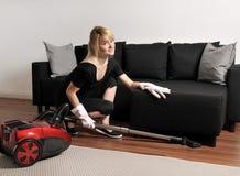 Η καθαρίζοντας κυρία σκουπίζει τον καναπέ με ηλεκτρική σκούπα Στοκ εικόνες με δικαίωμα ελεύθερης χρήσης