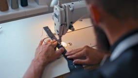 Η καθιερώνουσα τη μόδα γενειοφόρος μοδίστρα εργάζεται στη ράβοντας μηχανή στο στούντιο σχεδίου μόδας φιλμ μικρού μήκους