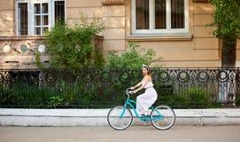 Η καλή γυναίκα στο εκλεκτής ποιότητας ποδήλατο οδηγά κατά μήκος της οδού πόλεων στοκ εικόνες