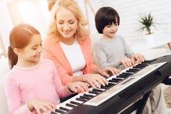 Η καλή ηλικιωμένη γυναίκα διδάσκει τα μικρά εγγόνια για να παίξει το συνθέτη στοκ φωτογραφίες με δικαίωμα ελεύθερης χρήσης