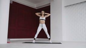 Η καλή νέα αθλητική γυναίκα εκτελεί τα κοντόχοντρα χέρια εκμετάλλευσης πίσω από το κεφάλι στο στούντιο ικανότητας ενάντια άσπρος  απόθεμα βίντεο