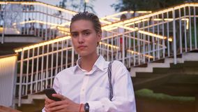 Η καλή σύγχρονη γυναίκα στέκεται στη γέφυρα, προσέχοντας στο smartphone, προσέχοντας στη κάμερα, σκάλα με τα φω'τα στο υπόβαθρο φιλμ μικρού μήκους