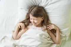Η καλημέρα, κορίτσι παιδιών ξανθό με τα μακροχρόνια κυματιστά ξυπνώ τρίχας, τρίβει τα μάτια Σε ένα μαξιλάρι στο κρεβάτι, τοπ άποψ Στοκ Εικόνες