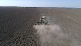 Η καλλιέργεια, μηχανή σποράς με το άροτρο σπέρνει το σιτάρι στο χώμα του τομέα στο φυτό της εποχής στην άνοιξη απόθεμα βίντεο