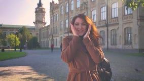 Η καλλιτεχνική συναισθηματική καυκάσια γυναίκα brunette είναι επίδειξη όπως τα σημάδια στη κάμερα και το χαμόγελο φυσικά στεμένος φιλμ μικρού μήκους