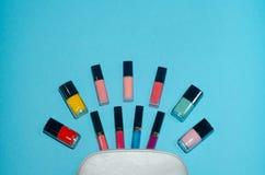 Η καλλυντική τσάντα γυναικών, αποτελεί τα προϊόντα ομορφιάς στο μπλε υπόβαθρο Κόκκινα, ρόδινα, ροδανιλίνης και μπλε κραγιόν Σύνολ Στοκ Εικόνες