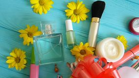 Η καλλυντική τσάντα makeup με τα διακοσμητικά καλλυντικά υποκύπτει στα μπλε ξύλινα λουλούδια, αρώματα απόθεμα βίντεο