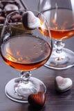 Η καραμέλα σοκολάτας με μορφή μιας καρδιάς εμπίπτει σε ένα ποτήρι του κονιάκ Στοκ Φωτογραφία