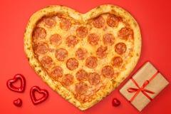 Η καρδιά διαμόρφωσε pepperoni πιτσών για την ημέρα βαλεντίνων με το κιβώτιο δώρων στο κόκκινο υπόβαθρο εγγράφου στοκ εικόνες