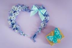 Η καρδιά που γίνεται από τον υάκινθο ανθίζει με τα κιβώτια τόξων και δώρων μεντών με την πεταλούδα στο πορφυρό υπόβαθρο χαιρετισμ Στοκ Εικόνα