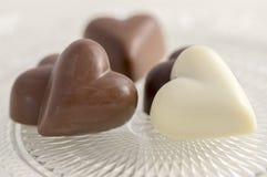 Η καρδιά τα γλυκά σοκολάτας, το καφετί και άσπρο χρώμα, διαφανές αναδρομικό πιάτο με τις πραλίνες στοκ φωτογραφία με δικαίωμα ελεύθερης χρήσης