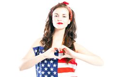 Η καρφίτσα επάνω στο κορίτσι που τυλίγεται στη αμερικανική σημαία με παραδίδει τη μορφή καρδιών Στοκ Εικόνες