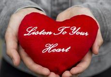 η καρδιά ακούει το σας Η καρδιά βελούδου με μια επιγραφή στα χέρια ακούει την καρδιά σας Στοκ φωτογραφία με δικαίωμα ελεύθερης χρήσης