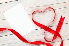 Η καρδιά ημέρας βαλεντίνων διαμόρφωσε την κόκκινη κορδέλλα και την κενή ευχετήρια κάρτα Στοκ εικόνα με δικαίωμα ελεύθερης χρήσης
