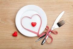 Η καρδιά ημέρας του βαλεντίνου διαμόρφωσε την κόκκινη κορδέλλα πέρα από το πιάτο με το silverwa Στοκ εικόνα με δικαίωμα ελεύθερης χρήσης