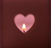 Η καρδιά διαμορφώνει την τρύπα που αποκόπτει στο σκούρο κόκκινο φως κεριών καψίματος υποβάθρου στο ρόδινο σκηνικό, ρομαντικό, περ Στοκ Φωτογραφία