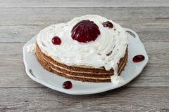 Η καρδιά διαμόρφωσε το κέικ με την κόκκινη μαρμελάδα που εξυπηρετήθηκε στο εκλεκτής ποιότητας πιάτο στο ξύλινο κλίμα Στοκ Εικόνες