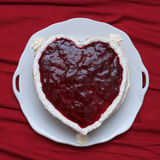 Η καρδιά διαμόρφωσε το κέικ με την κόκκινη μαρμελάδα που εξυπηρετήθηκε στο εκλεκτής ποιότητας πιάτο στην κόκκινη υφασματεμπορία Στοκ εικόνες με δικαίωμα ελεύθερης χρήσης