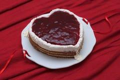 Η καρδιά διαμόρφωσε το κέικ με την κόκκινη μαρμελάδα που εξυπηρετήθηκε στο εκλεκτής ποιότητας πιάτο στην κόκκινη υφασματεμπορία Στοκ Φωτογραφίες