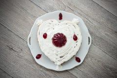 Η καρδιά διαμόρφωσε το κέικ με την κόκκινη μαρμελάδα που εξυπηρετήθηκε στο εκλεκτής ποιότητας πιάτο στο ξύλινο κλίμα Στοκ Φωτογραφίες