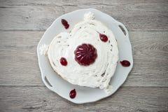 Η καρδιά διαμόρφωσε το κέικ με την κόκκινη μαρμελάδα που εξυπηρετήθηκε στο εκλεκτής ποιότητας πιάτο στο ξύλινο κλίμα Στοκ φωτογραφίες με δικαίωμα ελεύθερης χρήσης