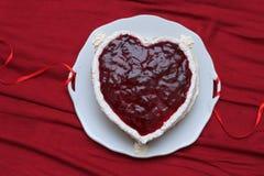 Η καρδιά διαμόρφωσε το κέικ με την κόκκινη μαρμελάδα που εξυπηρετήθηκε στο εκλεκτής ποιότητας πιάτο στην κόκκινη υφασματεμπορία Στοκ φωτογραφία με δικαίωμα ελεύθερης χρήσης