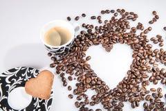 Η καρδιά κάνει τα φασόλια καφέ μορίων και κοιλαίνει το espresso μορίων και το μπισκότο αγαπημένων στο άσπρο υπόβαθρο Στοκ Εικόνες