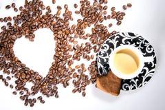 Η καρδιά κάνει τα φασόλια καφέ μορίων και κοιλαίνει το espresso μορίων και το μπισκότο αγαπημένων στο άσπρο επιτραπέζιο υπόβαθρο Στοκ Εικόνες