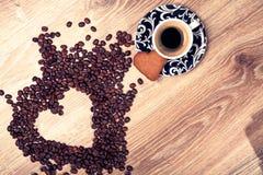 Η καρδιά κάνει τα φασόλια καφέ μορίων και κοιλαίνει το espresso μορίων και το μπισκότο αγαπημένων στο ξύλινο επιτραπέζιο υπόβαθρο Στοκ φωτογραφία με δικαίωμα ελεύθερης χρήσης
