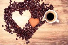Η καρδιά κάνει τα φασόλια καφέ μορίων και κοιλαίνει το espresso μορίων και το μπισκότο αγαπημένων στο ξύλινο επιτραπέζιο υπόβαθρο Στοκ Φωτογραφίες