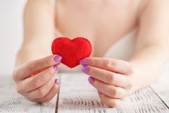 Η καρδιά στα χέρια, θηλυκό κρατά το χειροποίητο ραμμένο μαλακό παιχνίδι Στοκ Φωτογραφία