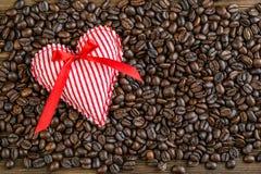 Η καρδιά υφάσματος στα φασόλια καφέ, ημέρα βαλεντίνων ή γιορτάζει την εικόνα αγάπης Στοκ Φωτογραφίες