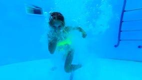 Η κατάδυση κοριτσιών κάτω από το νερό στην πισίνα και παρουσιάζοντας φυλλομετρεί επάνω απόθεμα βίντεο