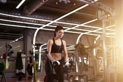 Η κατάλληλη γυναίκα εκτελεί την άσκηση με τη διασταύρωση καλωδίων άσκηση-μηχανών στη γυμναστική Στοκ Εικόνα