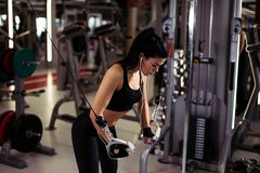 Η κατάλληλη γυναίκα εκτελεί την άσκηση με τη διασταύρωση καλωδίων άσκηση-μηχανών στη γυμναστική Στοκ φωτογραφίες με δικαίωμα ελεύθερης χρήσης