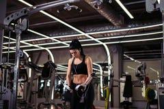 Η κατάλληλη γυναίκα εκτελεί την άσκηση με τη διασταύρωση καλωδίων άσκηση-μηχανών στη γυμναστική Στοκ Φωτογραφία