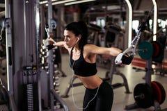Η κατάλληλη γυναίκα εκτελεί την άσκηση με τη διασταύρωση καλωδίων άσκηση-μηχανών στη γυμναστική Στοκ εικόνες με δικαίωμα ελεύθερης χρήσης