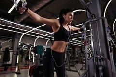 Η κατάλληλη γυναίκα εκτελεί την άσκηση με τη διασταύρωση καλωδίων άσκηση-μηχανών στη γυμναστική Στοκ Φωτογραφίες